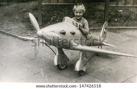 Vintage photo of little girl in toy plane, fifties - stock photo