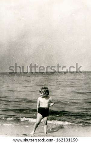 Vintage photo of little girl on beach, fifties - stock photo