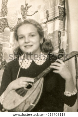 Vintage photo of little girl playing on mandolin (sixties) - stock photo