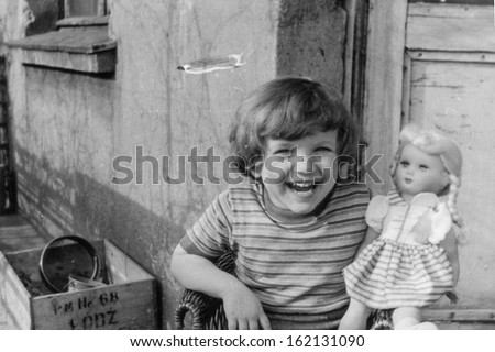 Vintage photo of little girl with a doll, fifties - stock photo