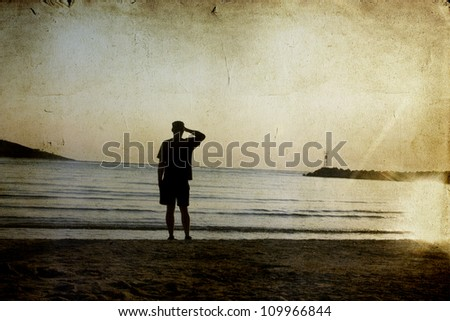 Vintage photo of lonely man watching the sunset on beach - stock photo