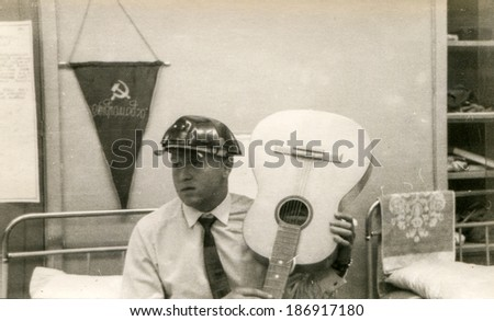 Vintage photo of man in hard hat holding a guitar (in Russia, 1970's) - stock photo
