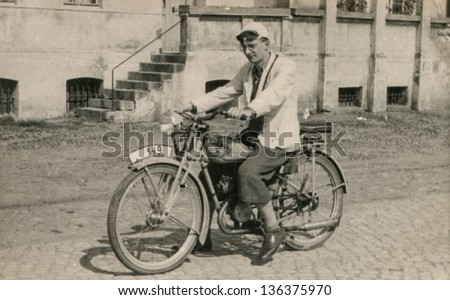 Vintage photo of man on motorbike, forties - stock photo