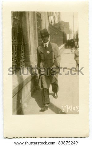 Vintage photo of man walking on the street (thirties) - stock photo