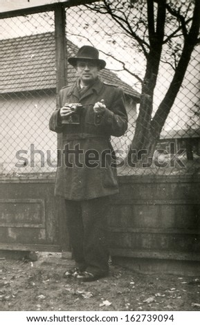 Vintage photo of man with a camera outdoor, fifties - stock photo