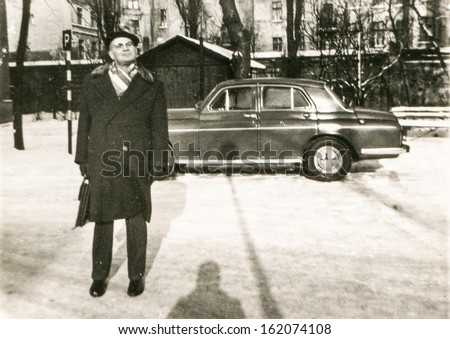 Vintage photo of man with an old car in background, fifties - stock photo