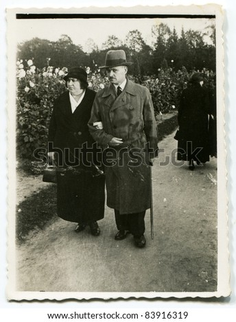 Vintage photo of mature couple walking (forties) - stock photo