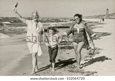 Vintage photo of mother and aunt with little girl on beach (fifties)