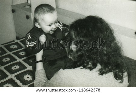 Vintage photo of mother and baby daughter (early eighties) - stock photo