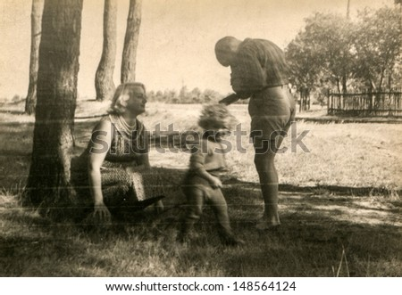 Vintage photo of mother and children in forest (fifties) - stock photo