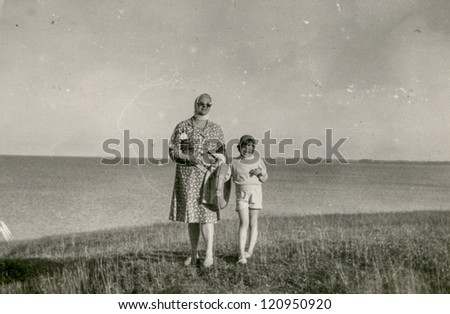 Vintage photo of mother and daughter at seaside (fifties) - stock photo