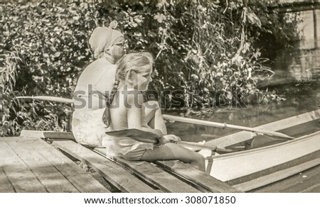 Vintage photo of mother and daughter during a kayak trip, 1950's - stock photo