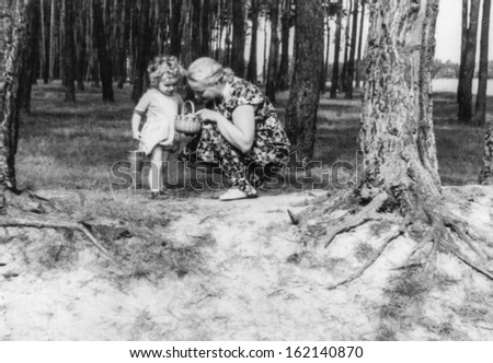 Vintage photo of mother and daughter in forest, fifties - stock photo