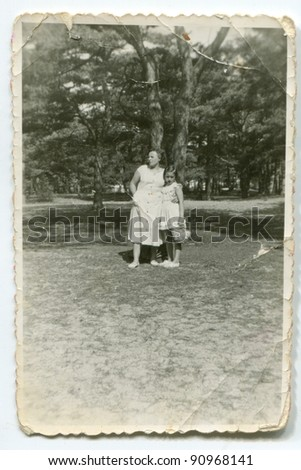 Vintage photo of mother and daughter in garden (fifties) - stock photo