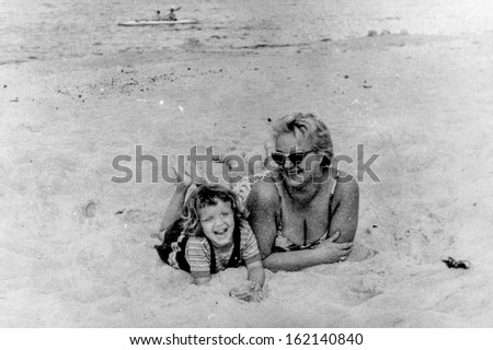 Vintage photo of mother and daughter on beach, fifties - stock photo