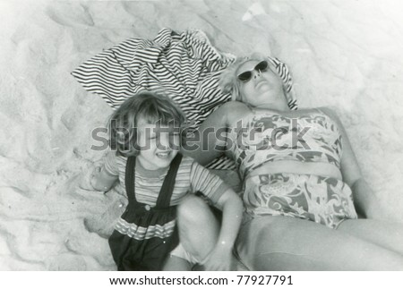 Vintage photo of mother and daughter on beach (fifties) - stock photo