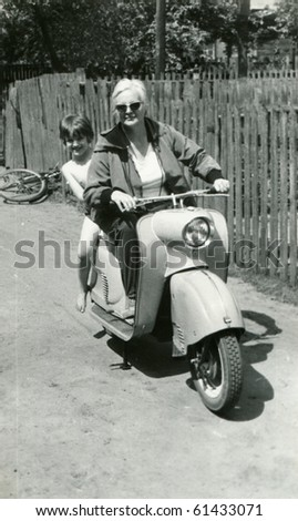 Vintage photo of mother and daughter on scooter (early sixties) - stock photo