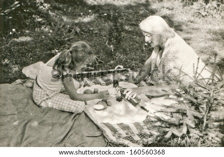 Vintage photo of mother and daughter picnicking, sixties - stock photo