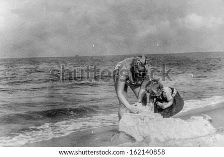 Vintage photo of mother and daughter playing on beach, fifties - stock photo