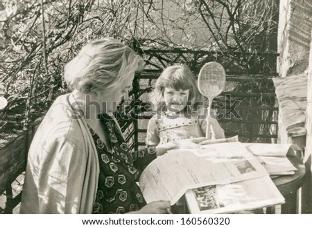 Vintage photo of mother and daughter reading on balcony, sixties - stock photo