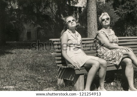 Vintage photo of mother and daughter tanning on bench in park (sixties)