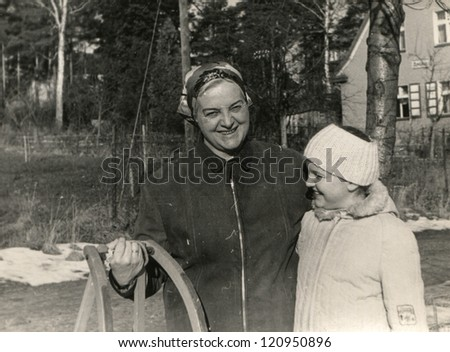 Vintage photo of mother and daughter with sled (early sixties)