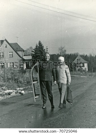 Vintage photo of mother and daughter with sled (sixties) - stock photo