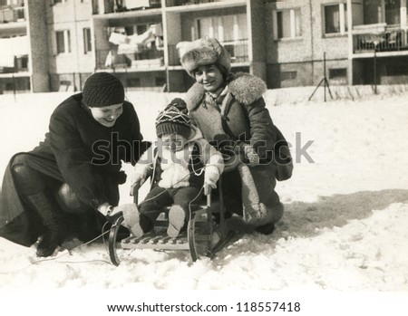 Vintage photo of mother, aunt and baby girl in winter (eighties) - stock photo