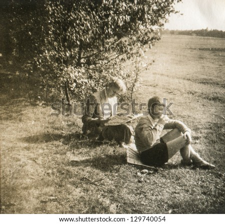 Vintage photo of mother reading a newspaper outdoor and his son, fifties