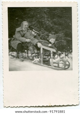 Vintage photo of mother riding on sledge with her children (fifties) - stock photo