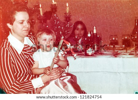 Vintage photo of mother with little daughter at Christmas party (early eighties) - stock photo
