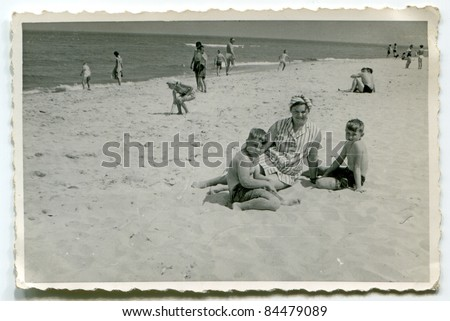 Vintage photo of mother with sons on beach (fifties)
