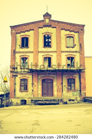 Vintage photo of old abandoned building with windows in old town. - stock photo