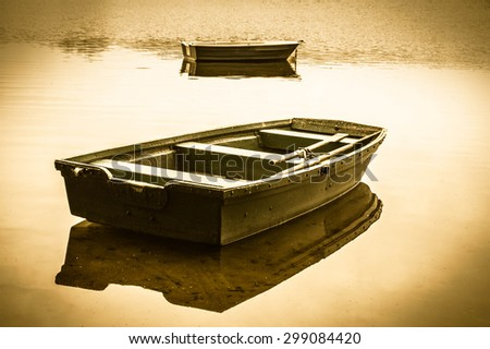 Vintage photo of old boat for fishing on the lake, quiet surface of water. Nature background, vintage effect. - stock photo