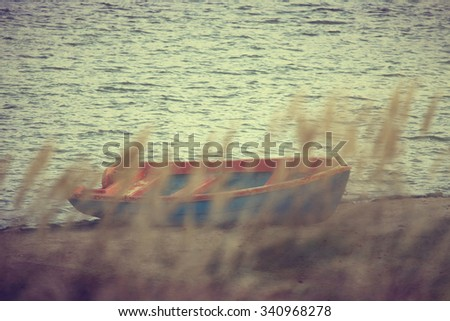Vintage photo of old boat for fishing on the lakeNature background, vintage effect and INK modern filter  - stock photo