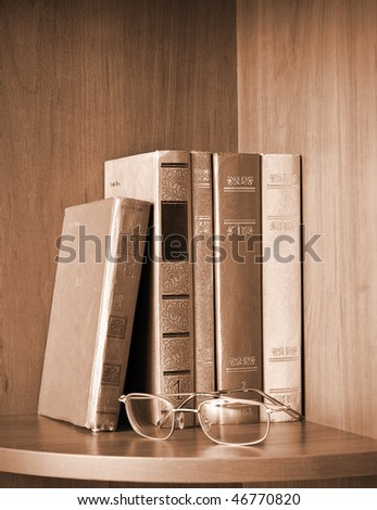 Vintage photo of old books and glasses on a shelf - stock photo