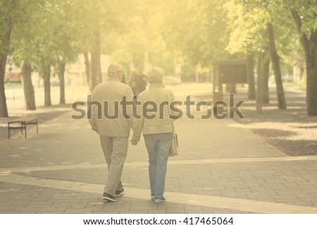 Vintage photo of old couple walking in the park a sunny day - stock photo