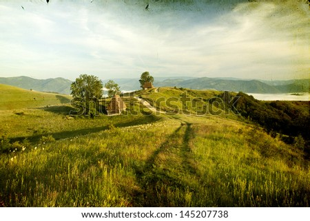 Vintage photo of old house in the mountains in the sunrise - stock photo