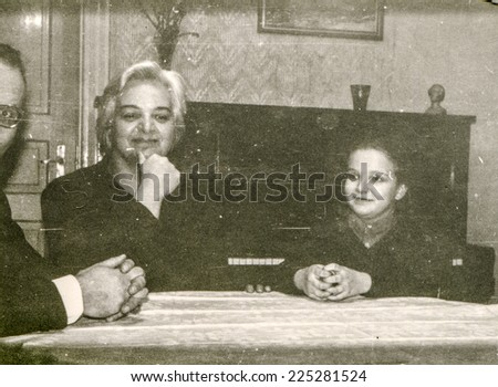 Vintage photo of parents sitting at the table with little girl, fifties - stock photo