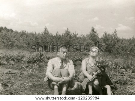 Vintage photo of parents with little daughter resting outdoor (fifties) - stock photo