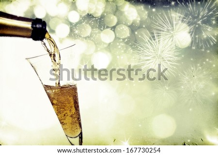 Vintage photo of pouring champagne against holiday lights   - stock photo