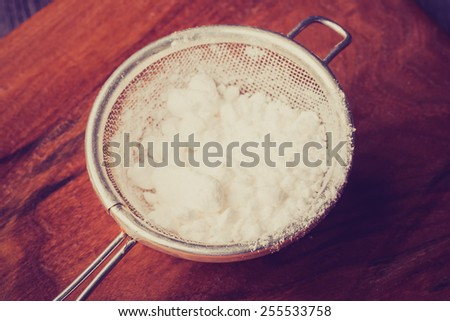 Vintage photo of powdered sugar in a sieve - stock photo