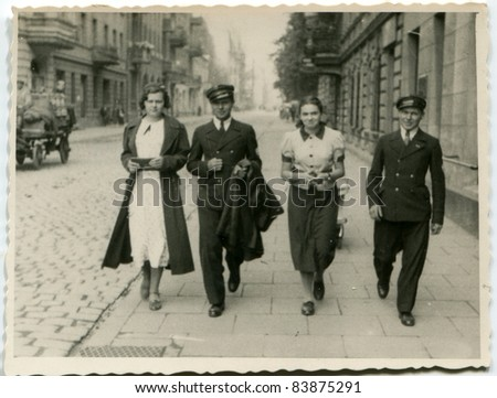 Vintage photo of pupils in school uniforms walking on the street (thirties) - stock photo