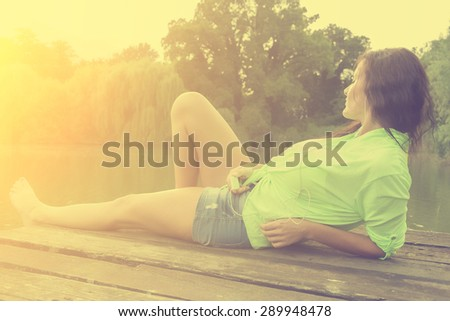 Vintage photo of relaxing woman listening music in summer sunset - stock photo