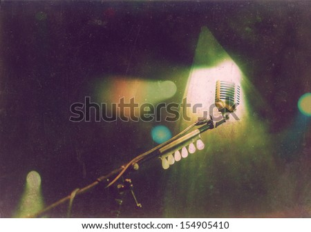Vintage photo of retro styled microphone in stage lights during concert - stock photo
