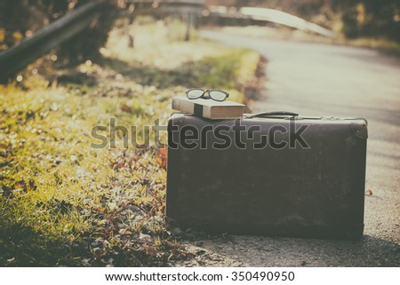 Vintage photo of retro suitcase and book - stock photo