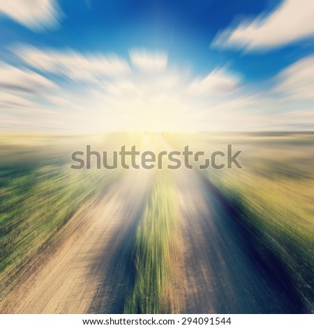 Vintage photo of road in country and field motion blur with sunlight.