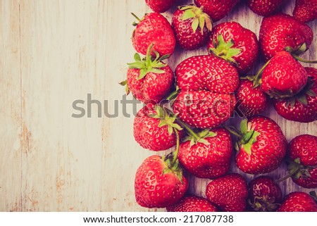 vintage photo of scattered strawberries on wooden table - stock photo