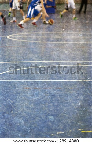Vintage photo of school gym floor with out of focus legs of children playing basketball in the background - stock photo