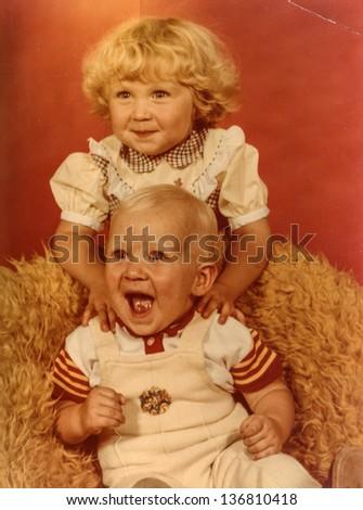 Vintage photo of siblings (early eighties) - stock photo